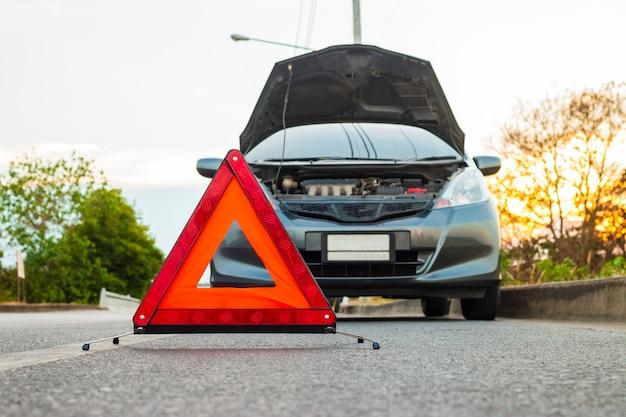 Nieoczekiwana sytuacja, znak zatrzymania awaryjnego i zepsuty samochód miejski na drodze.
