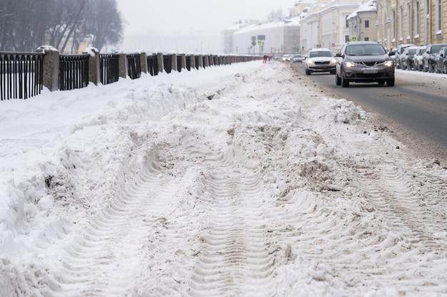 Nieoczyszczona ulica z ciężkimi zaspami po śniegu w mieście, samochody na drodze na tle. zimowa zła pogoda.