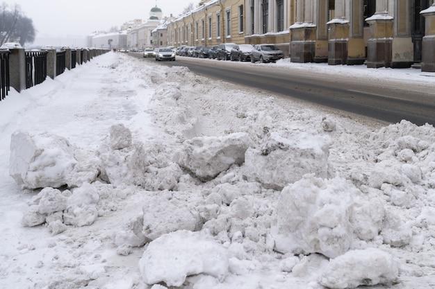 Nieoczyszczona ulica z dużymi zaspami śnieżnymi po opadach śniegu w mieście. zimowa zła pogoda.