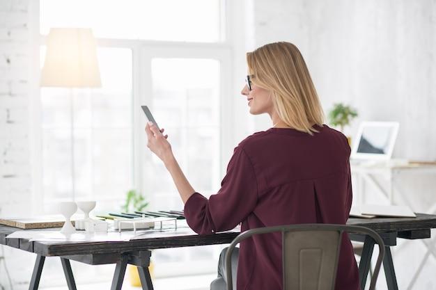 Nieodebrane połączenie. zadowolony atrakcyjny bizneswoman siedzi na krześle i gapi się na telefon