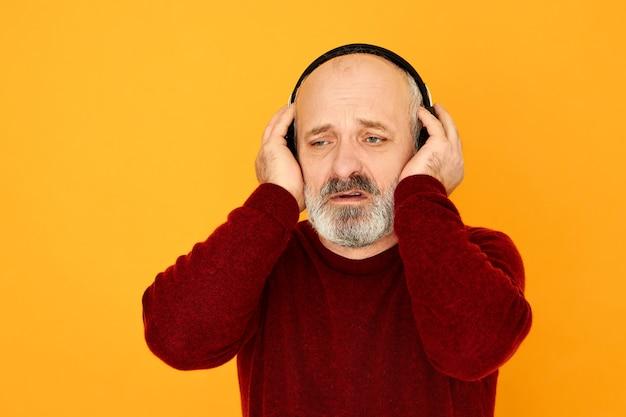 Nieogolony łysy mężczyzna na emeryturze pozuje odizolowany w bezprzewodowych słuchawkach, trzymając ręce na uszach, słuchając meczu piłki nożnej w sportowej transmisji radiowej, ma niezadowolony, zdenerwowany wygląd, ponieważ jego drużyna przegrała