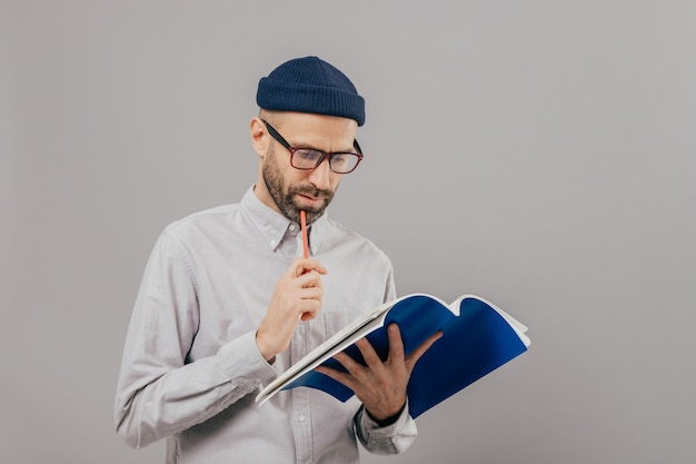 Nieogolony mężczyzna trzyma długopis, patrzy uważnie w otwartą książkę