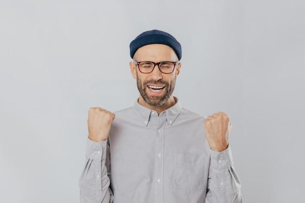 Nieogolony mężczyzna unosi zaciśnięte pięści, nosi okulary i formalną koszulę, świętuje swój triumf