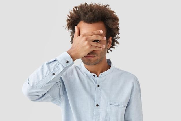 Nieogolony młody kędzierzawy mężczyzna zakrywa oczy dłonią, próbuje się ukryć, patrzy przez palce