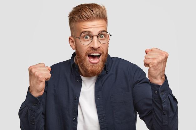 Nieogolony rudy młody zwycięzca zaciska pięści ze szczęścia, szeroko otwiera usta, pewny swojego sukcesu, ubrany w modną koszulę i okulary, stoi na białej ścianie