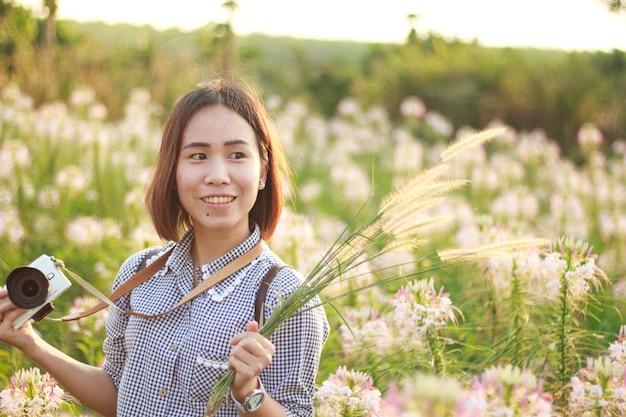 Nieokreślona kobieta robi zdjęcia podczas wizyty vintage kwiatowy ogród