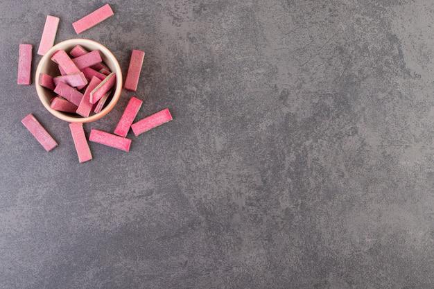 Nieopakowane patyczki gumy do żucia bez cukru umieszczone w misce.
