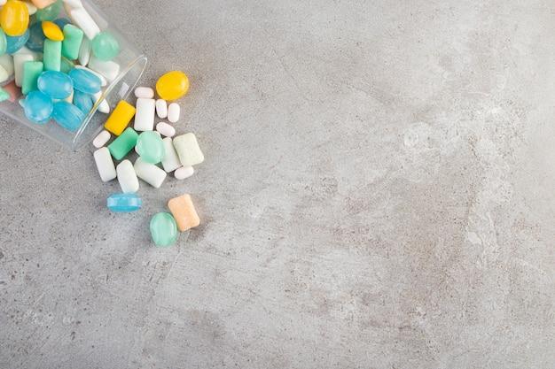 Nieopakowane patyczki gumy do żucia bez cukru umieszczone w szklanym kubku.