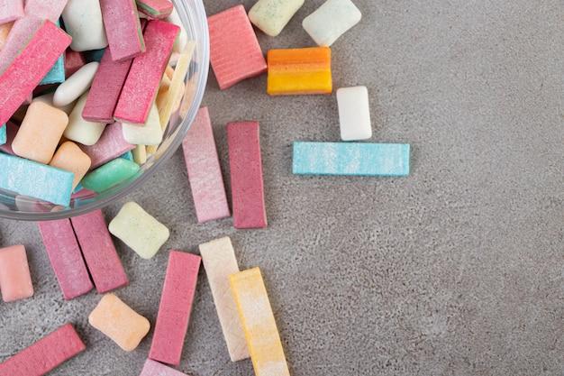 Nieopakowane patyczki gumy do żucia bez cukru umieszczone w szkle.