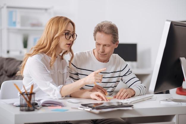 Nieopanowany flirtujący starzejący się biznesmen siedzi w biurze i pracuje nad projektem, flirtując i wpatrując się w młodego kolegę