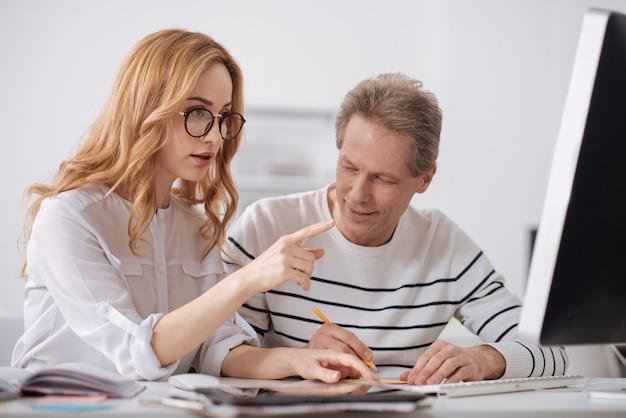 Nieopanowany, zabawny starszy menedżer siedzi w biurze i pracuje nad projektem, flirtuje i gapi się na młodego kolegę