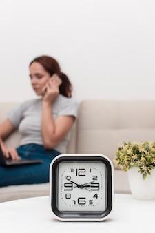 Nieostra kobieta rozmawia przez telefon z zegarem