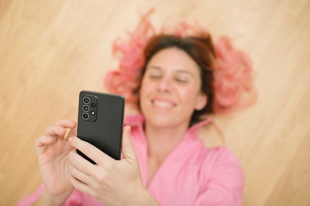Nieostre kobieta ubrana na różowo, leżąca na ziemi, używająca telefonu komórkowego na pierwszym planie