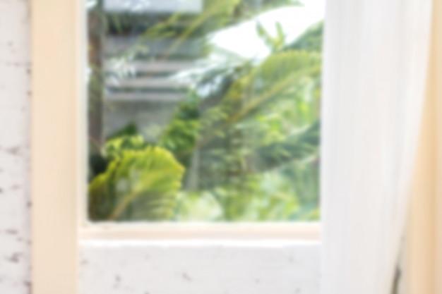 Nieostre tło okna z białymi zasłonami w porannym czasie.
