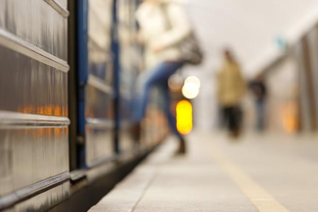 Nieostre tło peronu metra, ludzie wsiadają do pociągu