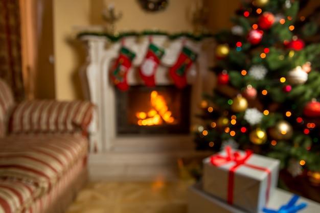 Nieostre tło z salonem ozdobionym na boże narodzenie z płonącym kominkiem