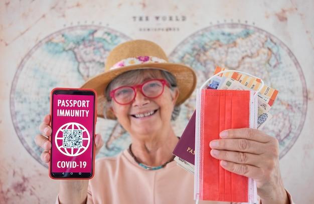 Nieostre, uśmiechnięta starsza kobieta trzymająca telefon komórkowy z certyfikatem zdrowia paszportu zielonej karty