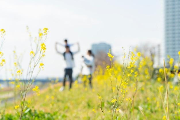 Nieostre zdjęcia rodziców i dzieci spacerujących po polu z uśmiechem