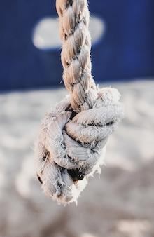 Nieostrość białej, zużytej liny z węzłem