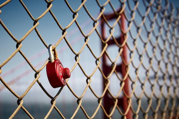 Nieostrość czerwonej kłódki zwisającej z ogrodzenia z siatki drucianej