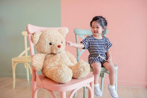 Nieostrość dwóch lat dziecko siedzi z jej pluszowego misia