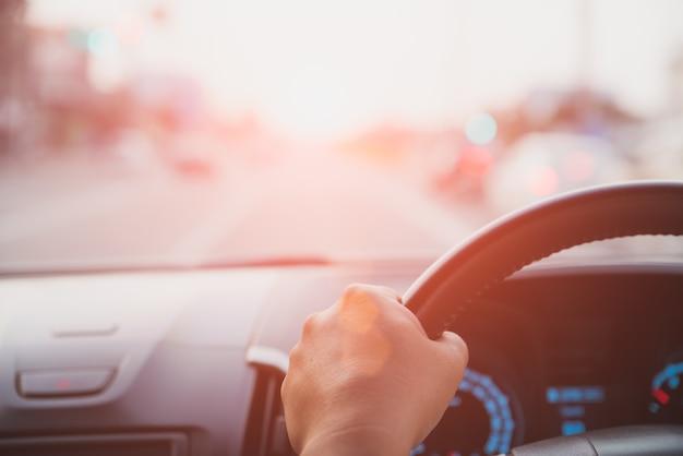 Nieostrość kierowca ręka trzyma kierownicę podczas jazdy na drodze.