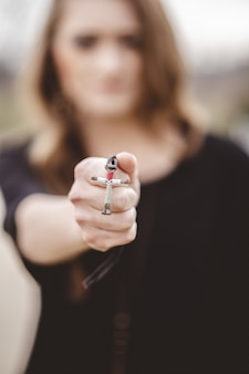 Nieostrość kobieta trzyma krzyż naszyjnik