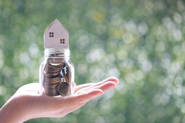 Nieostrość kobiety ręki trzymającej model domu na monetach pieniądze w szklanej butelce na naturalnym zielonym tle, inwestycje biznesowe i koncepcja nieruchomości