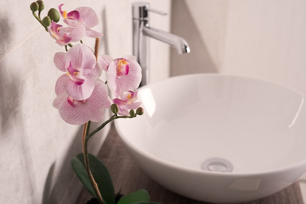 Nieostrość kwiatu orchidei obok umywalki w łazience