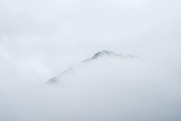 Nieostrość. minimalistyczny krajobraz górski. wspaniały minimalistyczny krajobraz z dużymi ośnieżonymi szczytami górskimi nad niskimi chmurami. nastrojowy minimalizm z dużymi szczytami gór ośnieżonych na zachmurzonym niebie.
