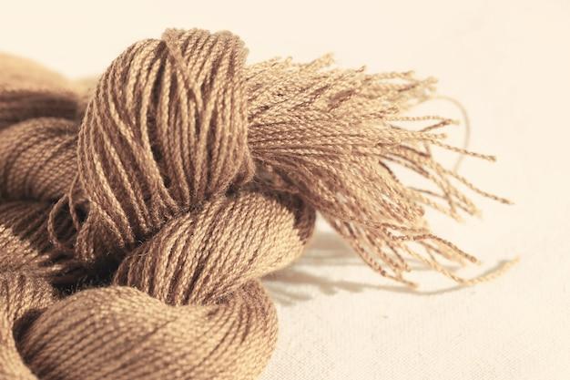 Nieostrość nici bawełnianej na abstrakcyjnym tle, stonowanych kolorach.
