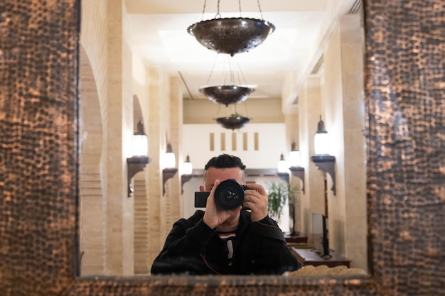 Nieostrość selektywnej ostrości obiektywu z zamazanym fotografem płci męskiej robienia sobie zdjęcia w lustrze