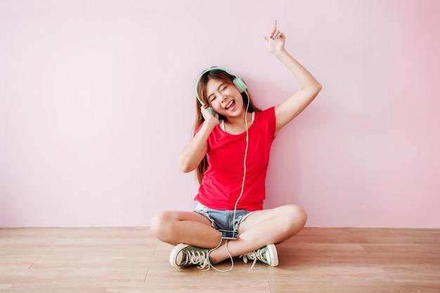 Nieostrość szczęśliwa młoda kobieta słuchania muzyki z telefonu komórkowego w domu