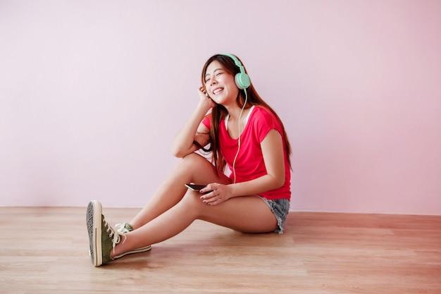 Nieostrość szczęśliwa młoda kobieta słuchania muzyki z telefonu komórkowego
