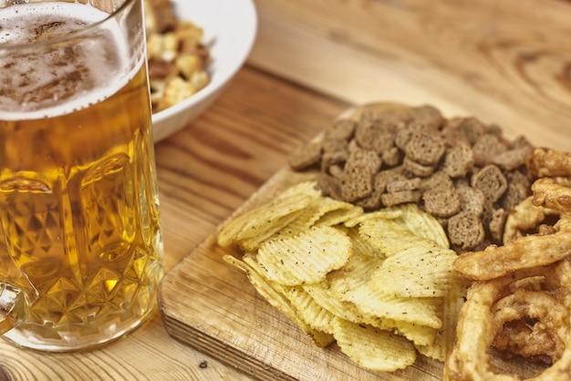 Nieostrość szklanki spienionego piwa rzemieślniczego z rozmytym jedzeniem na drewnianym stole