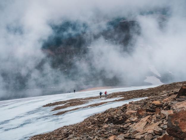 Nieostrość. turyści przybywają na szczyt mglistego, śnieżnego wzgórza. praca zespołowa i zwycięstwo, praca zespołowa ludzi w trudnych warunkach. trudna wspinaczka na szczyt góry.