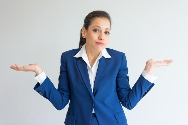 Nieostrożna biznesowa kobieta wzrusza ramionami ramiona.