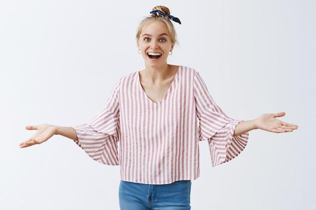 Nieostrożna i niezachwiana stylowa dziewczyna pozuje na białej ścianie