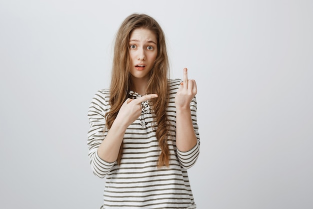 Nieostrożna niegrzeczna dziewczyna pokazuje środkowy palec na osobę