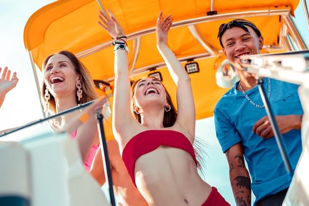 Nieostrożność młodości. dwie ładne beztroskie dziewczyny i uśmiechnięty młody mężczyzna z tatuażami bawią się latem na łodzi rekreacyjnej