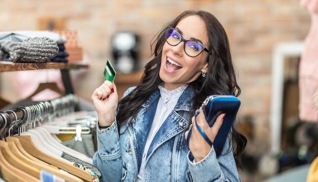 Nieostrożny klient zakupoholiczki trzyma torebkę i kartę kredytową ze szczęśliwym wyrazem wewnątrz sklepu z modą.