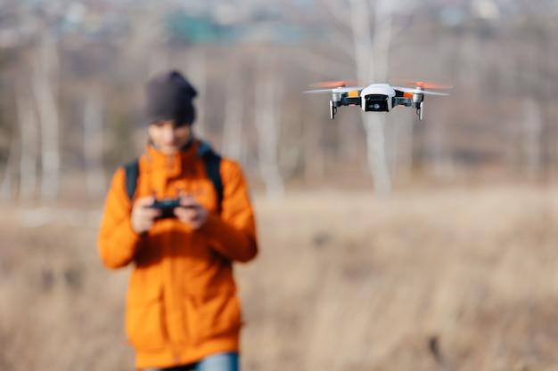 Nieostry mężczyzna kontroluje dron quadcopter na zewnątrz jesienią.