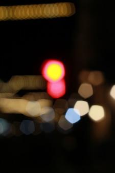 Nieostry piękny, błyszczący rozmazany bokeh samochodów i świateł drogowych w nocy.