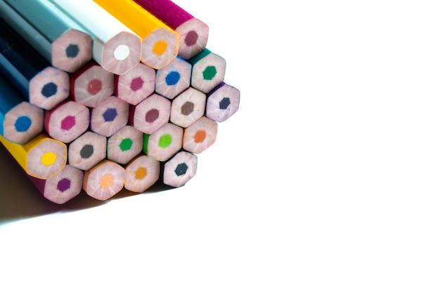Nieostrzone wielokolorowe ołówki na białym tle.