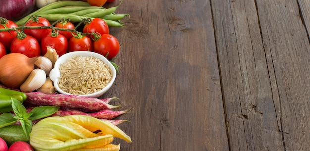 Nieoszlifowany surowy ryż i warzywa na brązowy drewniany stół z bliska