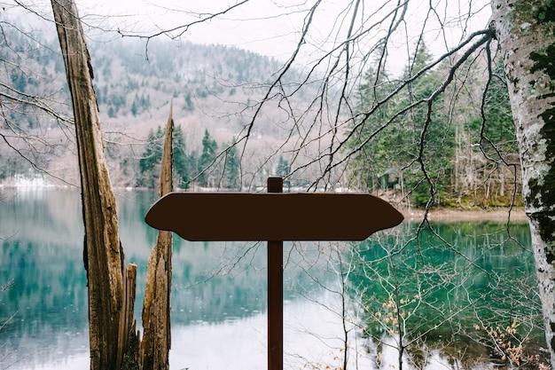 Nieoznakowany znak drogowy stoi w pobliżu jeziora w lesie