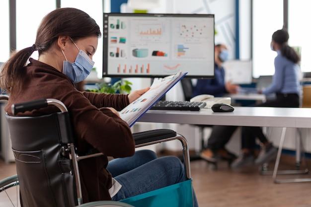Niepełnosprawna bizneswoman nosząca maskę medyczną chroniącą twarz przed koronawirusem
