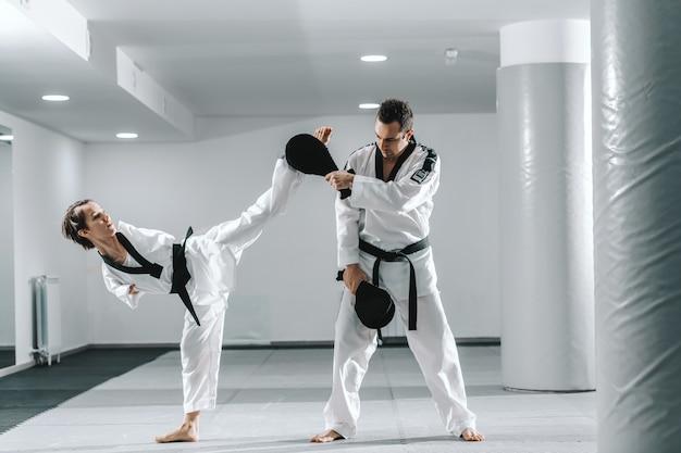 Niepełnosprawna dziewczyna ćwiczy taekwondo z jej treningiem.