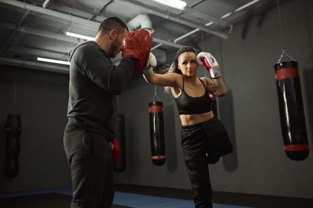 Niepełnosprawna dziewczyna jest zaangażowana w siłownię. kobieta z jedną nogą trenuje z trenerem w boksie, uczy się walczyć