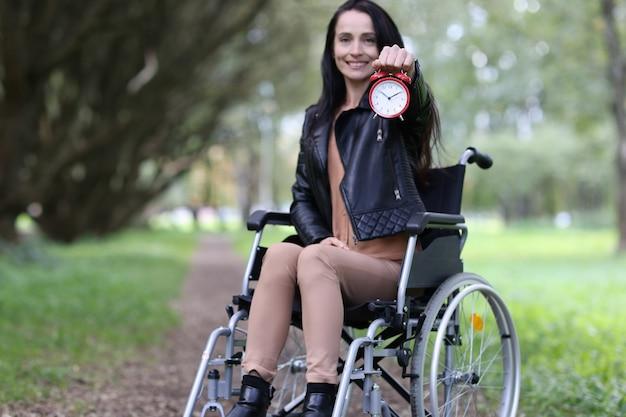 Niepełnosprawna kobieta na wózku inwalidzkim trzymająca czerwony budzik w parku nowe możliwości w życiu